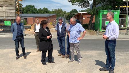 Die Ministerin lässt sich vor einer Baustelle die Planungen erklären.