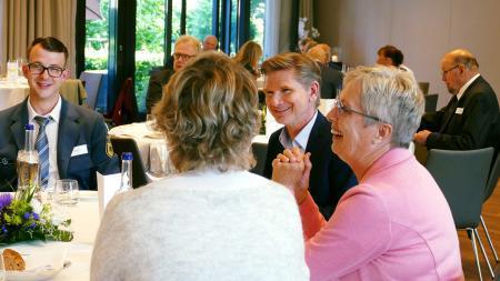 Minister Heiner Garg an einem Tisch mit Ehrenamtlichen.