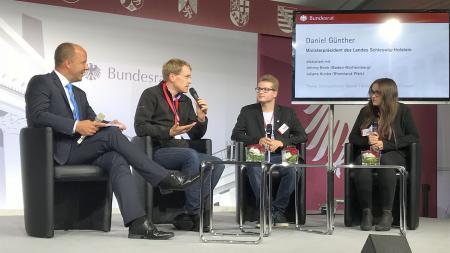 Ministerpräsident Daniel Günther diskutiert im Bundesrat-Zelt mit Jugendlichen.