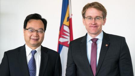 Zwei Männer stehen nebeneinander vor einer schleswig-holsteinischen Landesflagge.