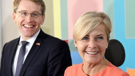 Ein Mann und eine Frau lächeln in die Kamera