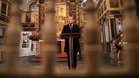 Ministerpräsident Daniel Günther steht in einer Kirche an einem Rednerpult.