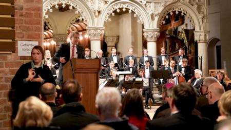 Ministerpräsident Daniel Günther steht an einem Rednerpult. Im Hintergrund ein Orchester, im Vordergrund die Gäste.