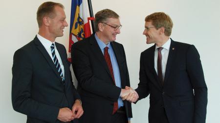 Drei Männer stehen vor der schleswig-holsteinischen Landesflagge, zwei von ihnen schütteln einander die Hand.