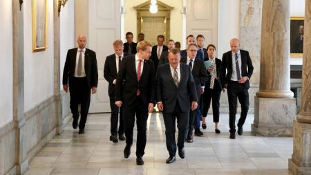 Zwei Männer unterhalten sich in einem säulengeschmückten Gang, hinter ihnen eine größere Menschengruppe.