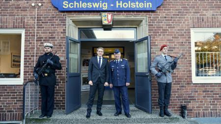 Ministerpräsident Günther und Oberst Güttler stehen vor einer geöffneten Tür, flankiert von zwei bewaffneten Soldaten.