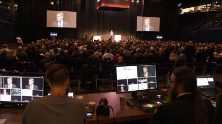 Zwei Personen sitzen vor Bildschirmen, dahinter viele Menschen die einem Mann auf der Bühne zuhören.