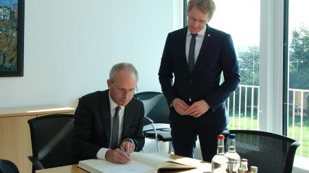 Botschafter Harris schreibt in das Gästebuch der Landesregierung, Ministerpräsident Günther schaut ihm dabei über die Schulter.