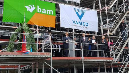 Eine Menschengruppe steht auf einem Baugerüst, links von ihnen steht ein Kranz.