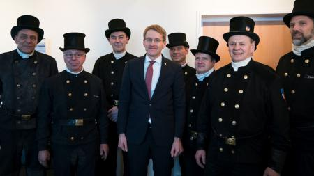 Ministerpräsident Daniel Günther mit mehreren Schornsteinfegern.