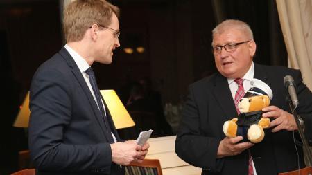 Landtagspräsident Klaus Schlie (r.) überreicht einen Teddybären in Polizeiuniform an Ministerpräsident Daniel Günther.