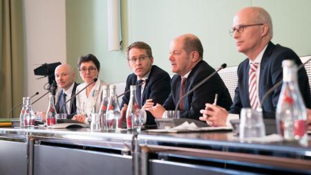 Fünf Personen sitzen an einem Tisch, vor ihnen stehen Mikrofone. V.l.n.r.: Staatssekretär Philipp Nimmermann, Finanzministerin Monika Heinold, Ministerpräsident Daniel Günther, Erster Hamburger Bürgermeister Olaf Scholz, Finanzsenator Peter Tschentscher.