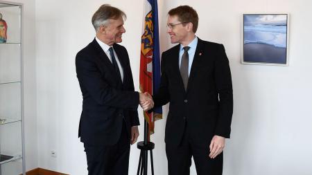 Ministerpräsident Günther (r.) und Botschafter Petersen schütteln sich vor einer Landesflagge die Hand.
