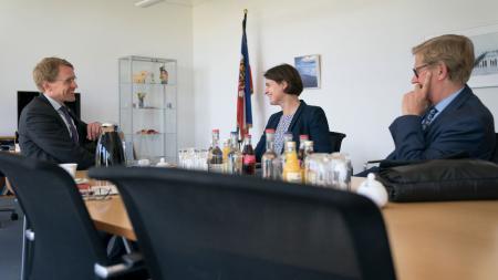 Ministerpräsident Daniel Günther (v.l.), DOSB-Chefin Veronika Rücker und der Präsident des Landessportverbands, Hans-Jakob Thiessen, sitzen an einem Tisch.