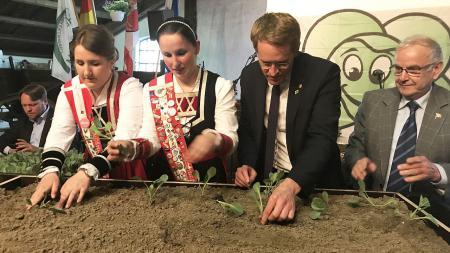 Ein Mann im Anzug steht neben zwei Frauen in Tracht. Gemeinsam pflanzen sie Kohl in einem Hochbeet.