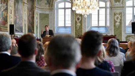 Ein Mann steht in einem prunkvollen Saal vor zahlreichen sitzenden Gästen und hält eine Rede.