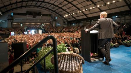 Ein Mann steht an einem Rednerpult und schaut auf eine große Menschenmenge in einer Halle.