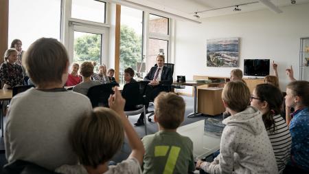 Ein Mann sitzt mit vielen Kindern in einem Büro.