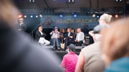 Vier Männer sitzen auf einer Bühne, (v.l.:) Uli Hase, der Landesbeauftragte für Menschen mit Behinderung, Rapper Graf Fidi und Moderator Markus Pingel.