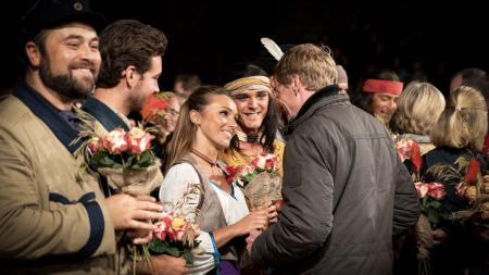 Ein Mann steht vor einer lächelnden kostümierten Frau und gibt ihr einen Blumenstrauß.