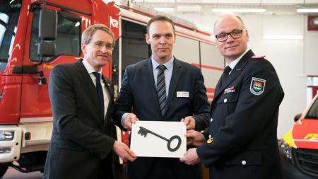 Ministerpräsident Daniel Günther (v. l.) und Kronshagens Bürgermeister Ingo Sander überreichten dem Leiter der Freiwilligen Feuerwehr Kronshagen, Christian Esselbach, symbolisch den Schlüssel zum neuen Gerätehaus.