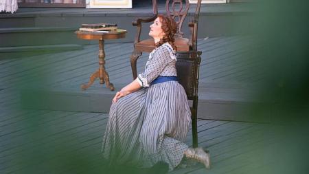 Eine Frau in einem ausladenden Kleid sitzt auf dem Boden vor einem Stuhl und schaut in die Ferne.