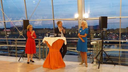 Ein Mann und zwei Frauen stehen an einem Tisch und unterhalten sich vor Publikum.