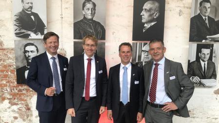 Mehrere Männer stehen vor einer Wand mit historischen Bildern.