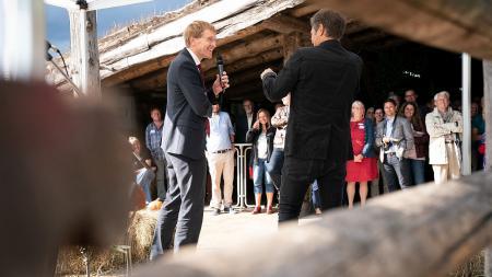 Zwei Männer im Gespräch stehen vor einem Publikum, einer hält ein Mikrofon in der Hand.