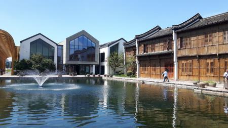 Blick über einen Teich mit Fontäne. Am Rand stehen moderne sowie traditionelle Holzhäuser.