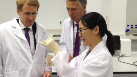 Zwei Männer in Laborkitteln schauen einer Frau dabei zu, wie sie ein Probenröhrchen mit einer Flüssigkeit füllt.