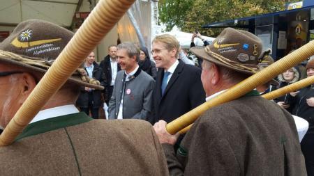 Zwei Männer stehen lachend vor einer Gruppe Männer in traditioneller bayrischer Kleidung mit Alphörnern in den Händen.