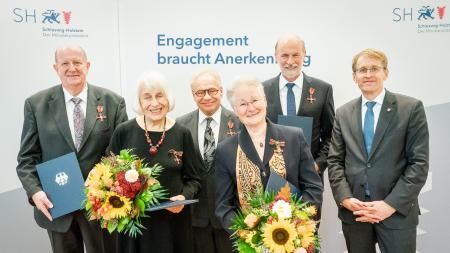 Menschengruppe mit Blumensträußen und Urkunden.