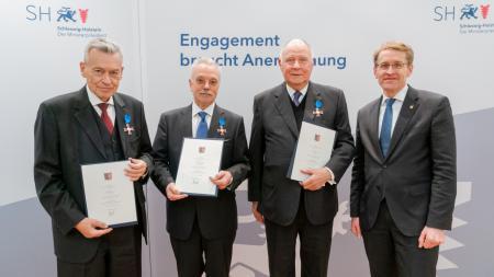 Vier Männer in Anzügen stehen nebeneinander.