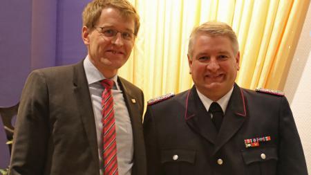 Wehrführer Marc Zielinski steht rechts neben Ministerpräsident Daniel Günther