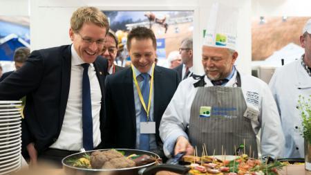 Zwei Männer schauen einem Koch beim Zubereiten einer typisch schleswig-holsteinischen Mahlzeit zu.