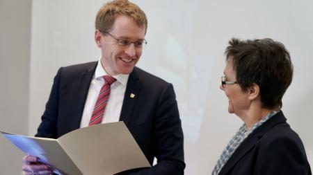 Ein Mann überreicht einer Frau eine Urkunde, beide Personen lächeln.