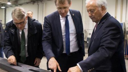 Drei Männer stehen vor einem langen Stück Metall. Einer der Männer erklärt den anderen etwas.