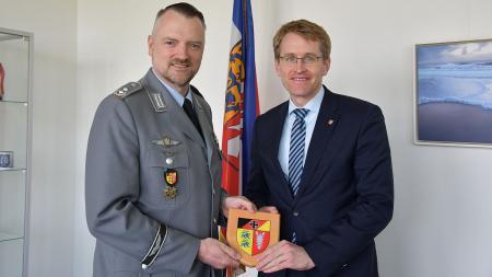 Oberstleutnant Dr. Marc Lemmermann (l.) überreichte Ministerpräsident Günther ein Wappen.