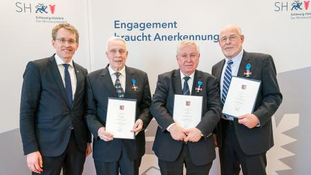Der Ministerpräsident steht links neben den drei Trägern des Landesordens