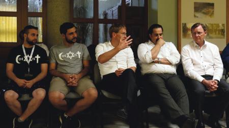 Fünf Männer sitzen nebeneinander auf Stühlen in einem Raum.