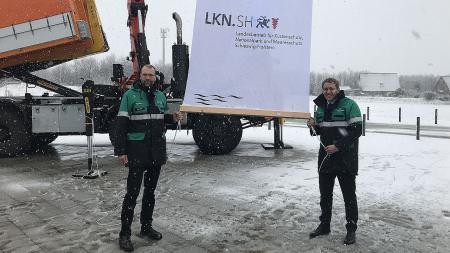 Ministerpräsident Günther und Direktor Oelerich halten im Schnee ein Plakat des Landesbetriebs hoch