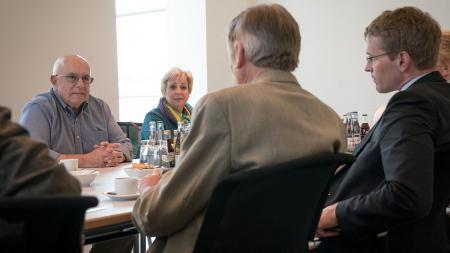 Vier Menschen sitzen an einem Tisch und unterhalten sich.