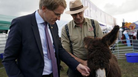 Ein Mann streichelt im Beisein eines anderen Mannes einen Esel.