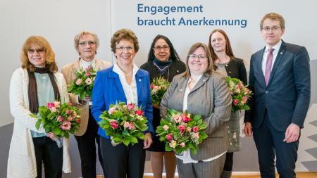Ministerpräsident Daniel Günther steht neben sechs Frauen.