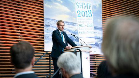 Ein Mann steht an einem Rednerpult und spricht zu Publikum.
