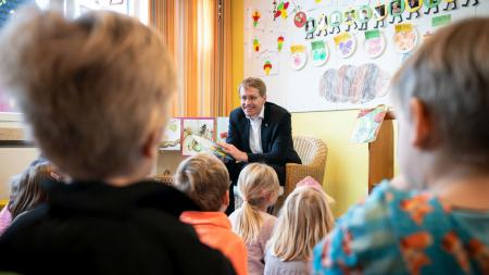 Ein Mann sitzt auf einem Stuhl und hat ein Buch in der Hand. Vor ihm sitzen viele Kinder.
