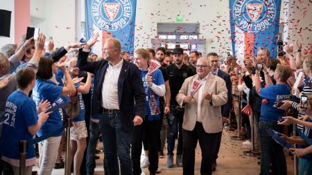 Eine jubelnde Menschenmasse steht Spalier für eine Gruppe junger Menschen. Im Hintergrund hängen Banner mit dem Wappen von Holstein Kiel von der Decke, es fliegt buntes Konfetti durch die Luft.