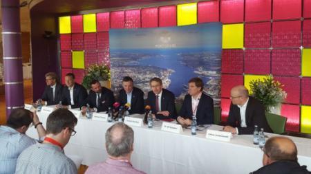 Sieben Männer sitzen nebeneinander an einem langen Tisch, vor ihnen knien Journalisten. Hinter ihnen hängt ein Luftbild des Kieler Hafens.