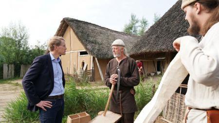 Ein Mann in moderner Kleidung unterhält sich mit zwei Männern in klassischer Wikinger-Kleidung.